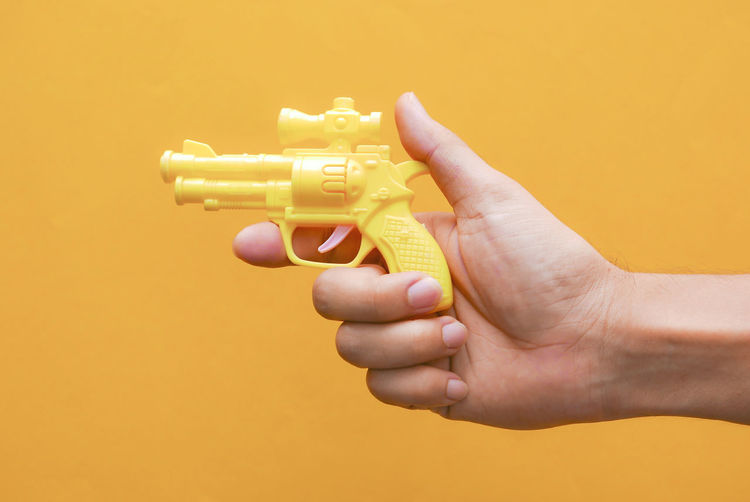 Close-up of person hand against yellow background