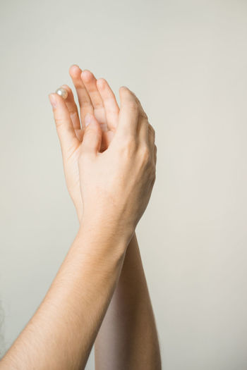 Cropped hands holding pearl against beige background