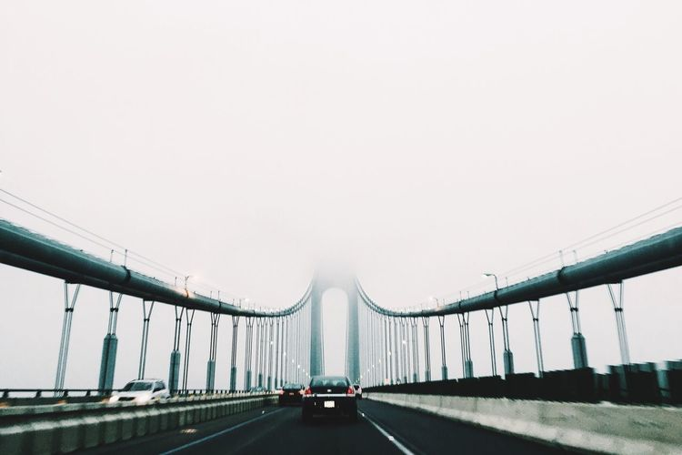 Car on verrazano–narrows bridge against sky during foggy weather