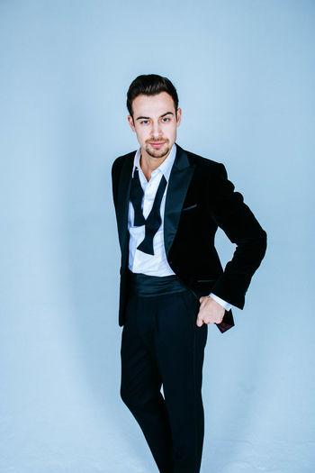 Portrait of businessman against blue background