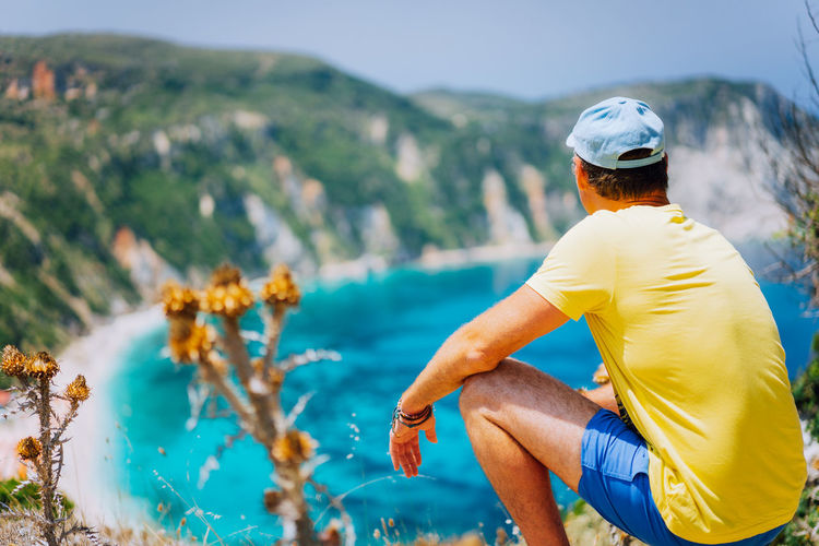 Rear View Of Man Sitting On Rock While Looking At Sea