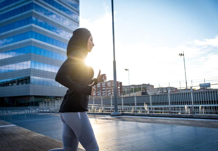 Man standing against buildings in city against sky