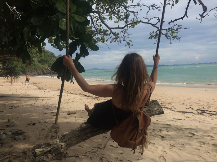 Rear view of woman swinging at beach against sky