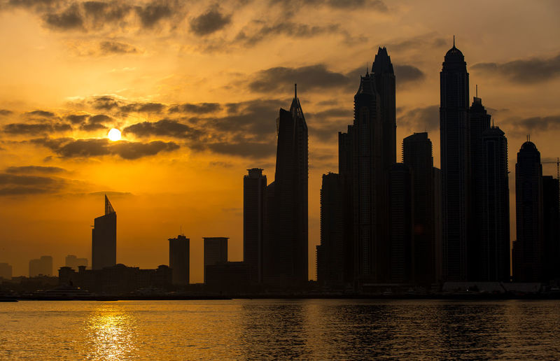 Sunny Looks Building Exterior Sunset Architecture Built Structure Sky Building City Water Skyscraper Tall - High Office Building Exterior Cloud - Sky Tower Waterfront Urban Skyline Nature Travel Destinations Orange Color Landscape No People Cityscape Modern Outdoors Financial District  Spire