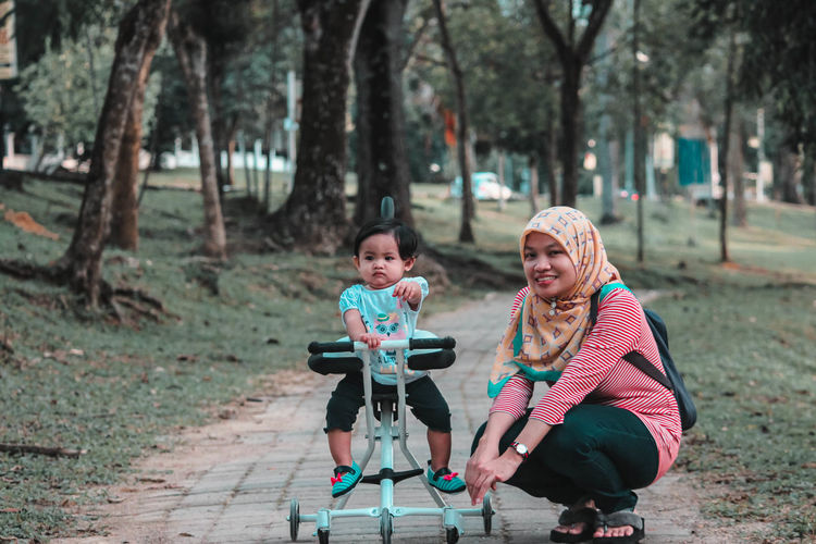 Full length portrait of mother with daughter on footpath at park