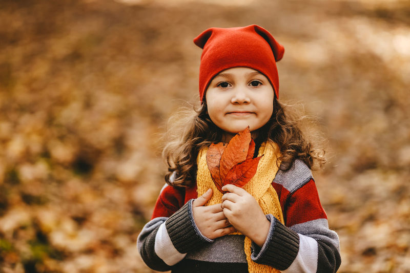 Portrait of a little girl a child in a warm hat walking holding an autumn leaf in the fall forest