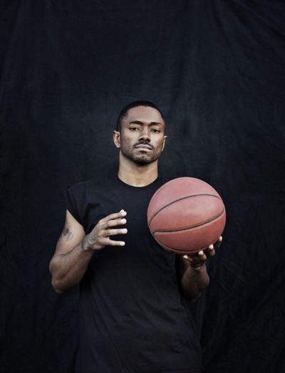 Portrait of young man holding ball while standing against black background