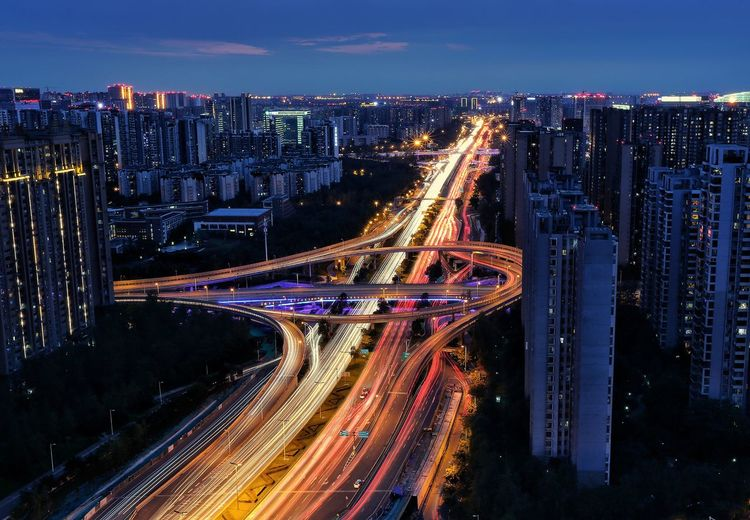 High angle view of light trails on highway amidst buildings