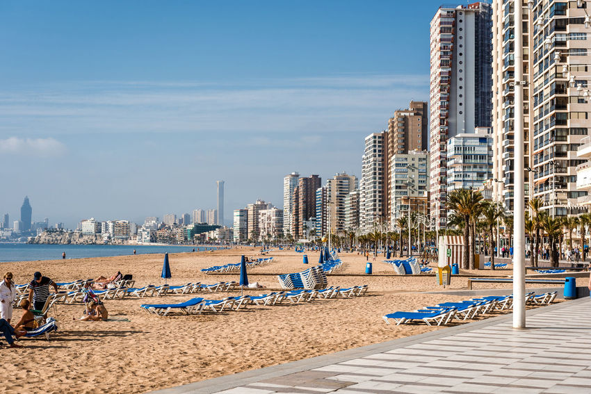 Benidorm, Spain - December 20, 2015: Beach of Benidorm. Benidorm is a coastal city in Alicante. Benidorm also known Beniyork because of the skyscrapers is a major beach destination for European tourism. Spain Alicante, Spain Beach Benidorm Buildings City Coast Comunidad Valenciana Contemporary Costa Blanca Deckchairs On The Sand Editorial  Europe Highrise Mediterranean Sea Modern Architecture Outdoors People Seashore Seaside Skyline Skyscrapers SPAIN Sunny Day Tourist Resort Travel Destinations
