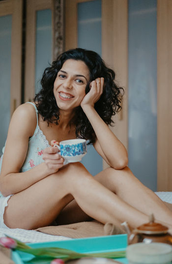 Portrait of smiling young woman drinking coffee while sitting at home