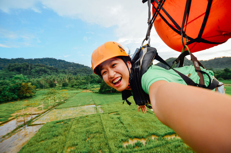 Portrait of smiling woman parasailing over field