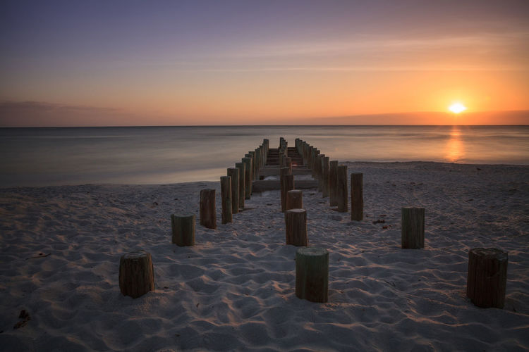 Wooden posts at sandy beach against sky during sunset