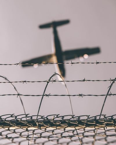 Low Angle View Of Airplane With Barbed Wire In Foreground