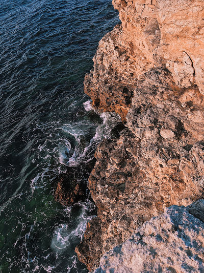 View from the top to the deep of the sea, the water beats on the stones, wave-like background