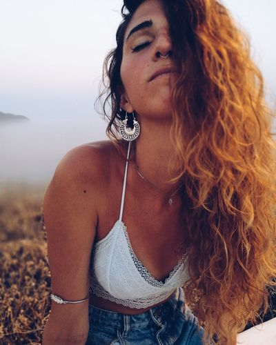 Beautiful young woman against sky