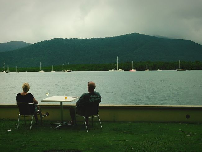 They are having a drink of a wine and beer on the table, while they are waiting for delivery dinner. And they are peaceful and look at beautiful view outside. Beautiful View Mountains Sky Light Rain Clouds Oceanfront Boats⛵️ People Are People Wine Glass Beer Glass Mobile Phone People And Nature People Looking At The Sea Beautiful Photo 👌