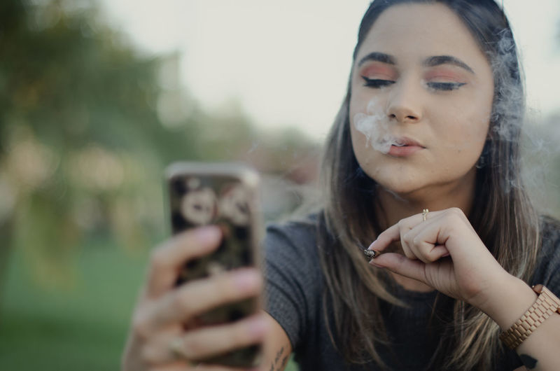 Young woman smoking cigarette using mobile phone