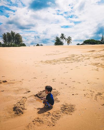 Kid sitting on sand at beach against sky