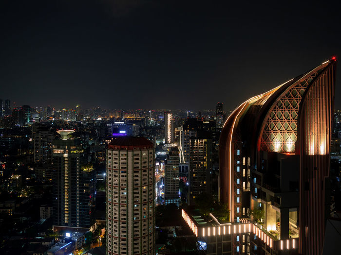 High angle view of illuminated buildings against clear sky at night