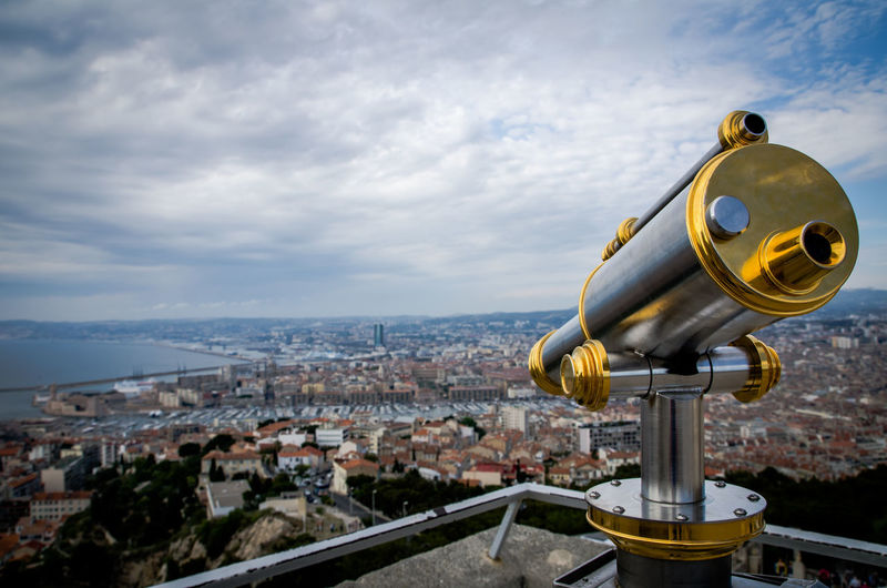 Close-up of hand-held telescope against cityscape