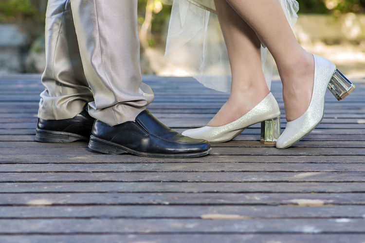 Low Section Of Couple Standing On Floorboard