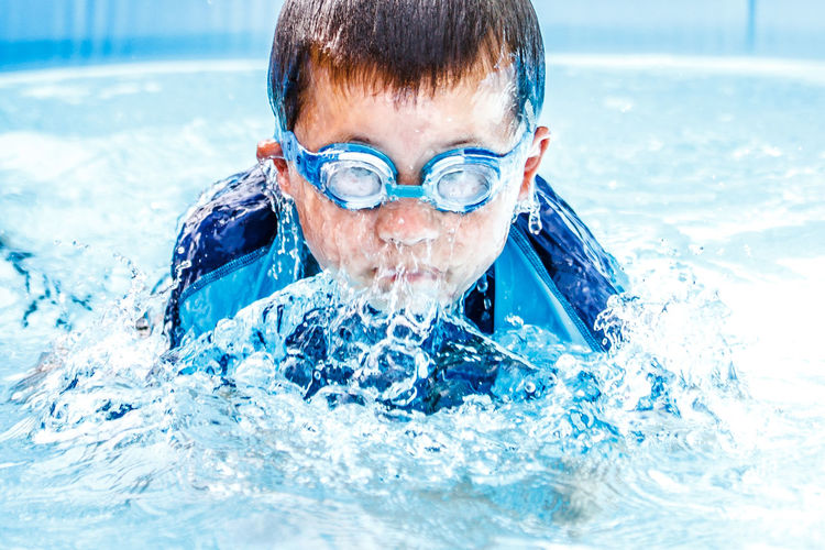 Boy Splashing Water In Swimming Pool