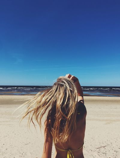 Rear view of young woman with blond hair standing at beach against blue sky