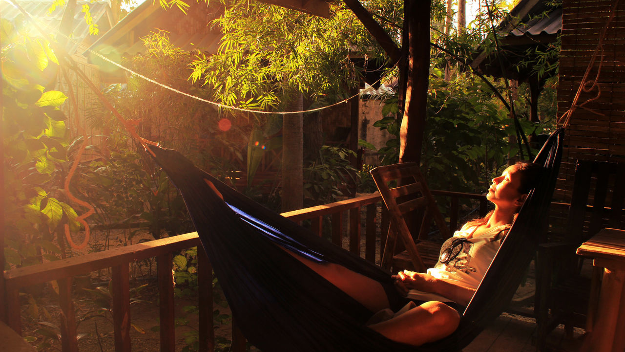 Young woman relaxing on hammock at tourist resort