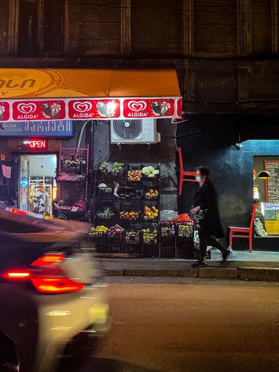 Blurred motion of man on illuminated city street at night