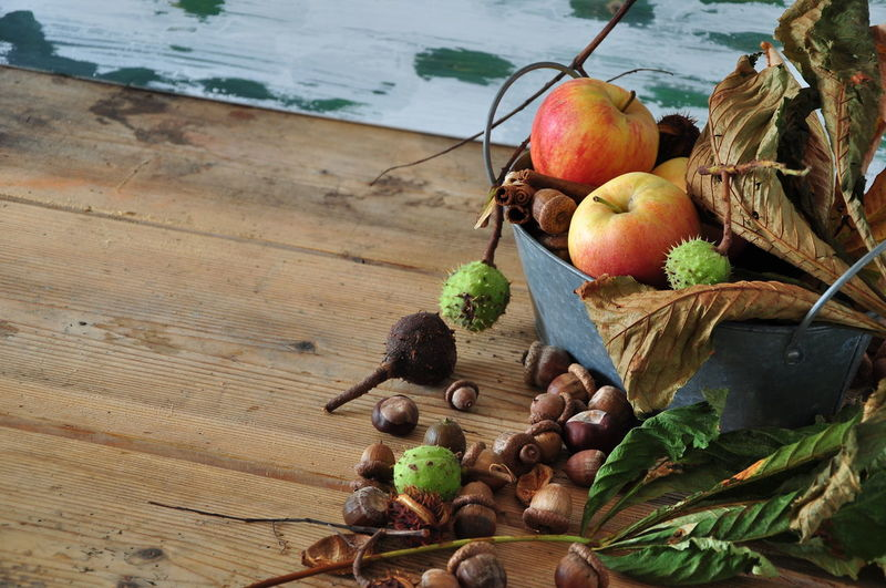 High Angle View Of Apples On Wooden Table Autumn Chestnut Copy Space Horizontal Apple - Fruit Basket Close-up Color Image Day Food Food And Drink Freshness Fruit Healthy Eating High Angle View Husk Indoors  Leaf No People Photography Season  Still Life Table Variation Wood - Material