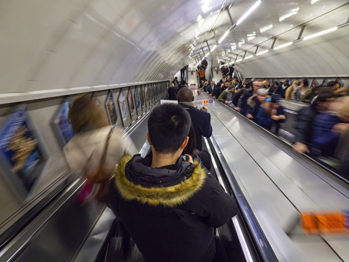 Long exposure of the people frenzy on an underground escalator