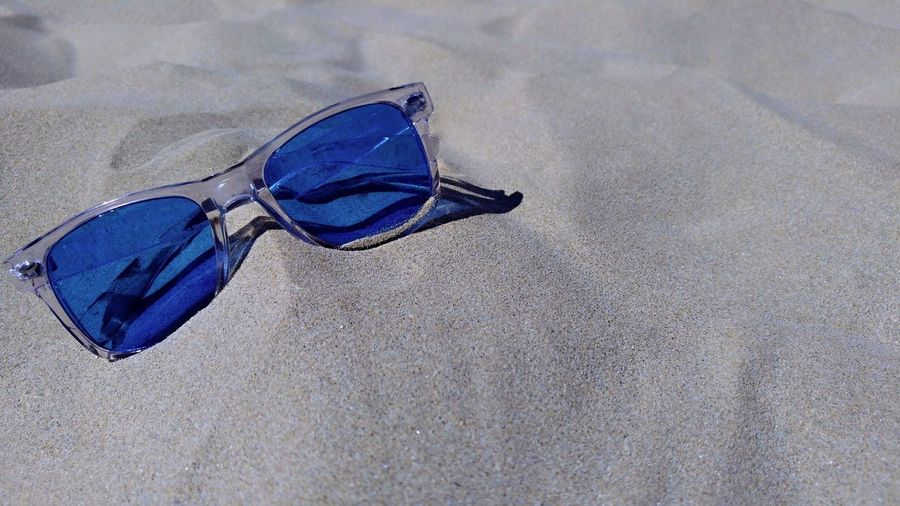 A pair of blue sunglasses lying on the sand of an Italian beach. Abandoned Beach Blue Close-up Day Fashion Glasses High Angle View Land Nature No People Outdoors Personal Accessory Protection Purple Sand Shoe Single Object Still Life Textile Wet