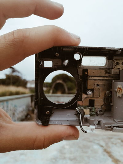 Cropped hand of person holding old camera