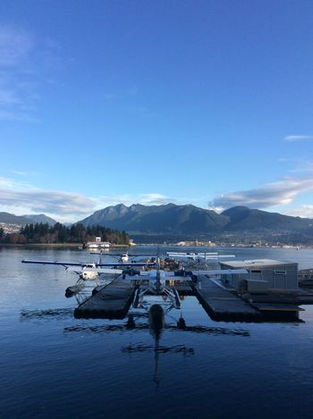 Vancouver Canada flying boats station Distant Mountains blue sky October Morning reflections in the harbour water White And Grey Clouds Industrial Waterfront Gas Station On Water