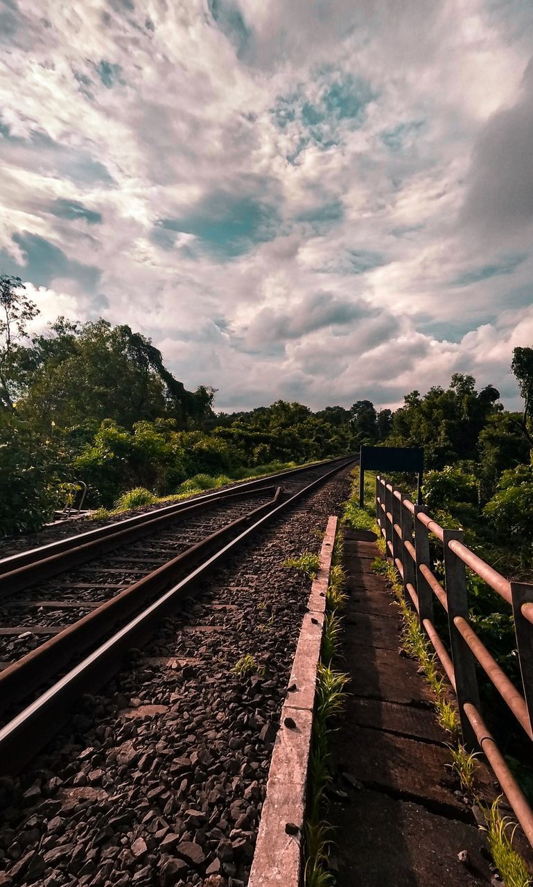 VIEW OF RAILROAD TRACKS ALONG TREES AND SKY