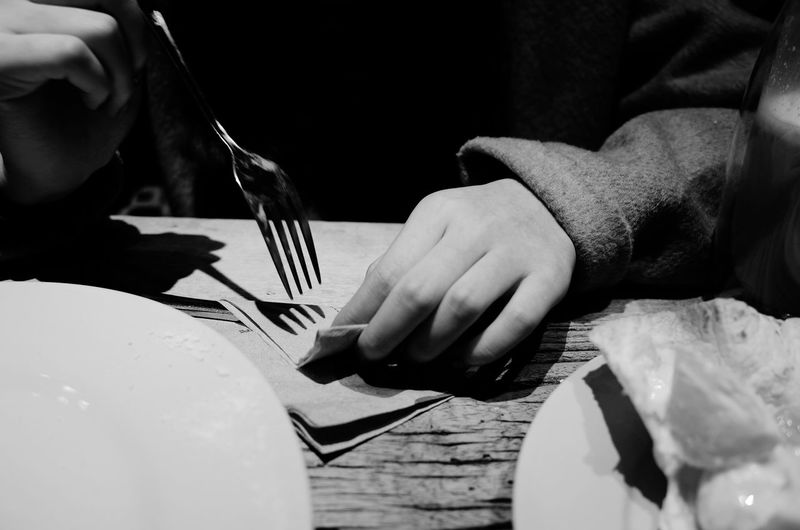 Midsection of person holding fork at table