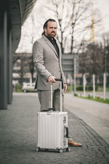 Portrait Focus On Foreground Business Man Business Money Suitcase Red Hair Beard Man With Beard Work Economy Mafioso Actor Jean-claude Knobbe Leipzig Well-dressed Suit Business Dress Grey Suit Black Shirt Pedestrian Acting