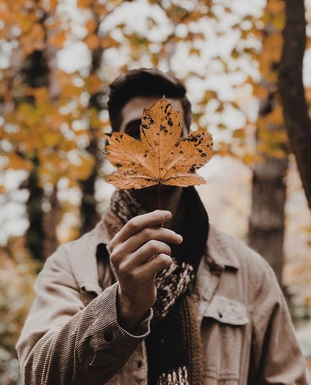 Man holding maple leaf while standing in park during autumn
