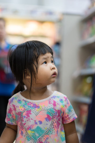 little girl walking in minimart and look up product for shopping Shopping Asian Girl Black Hair Casual Clothing Child Childhood Cute Females Floral Pattern Focus On Foreground Girls Hair Hairstyle Innocence Leisure Activity Lifestyles Look Up Looking Looking Away Mall Minimart One Person Portrait Real People Women