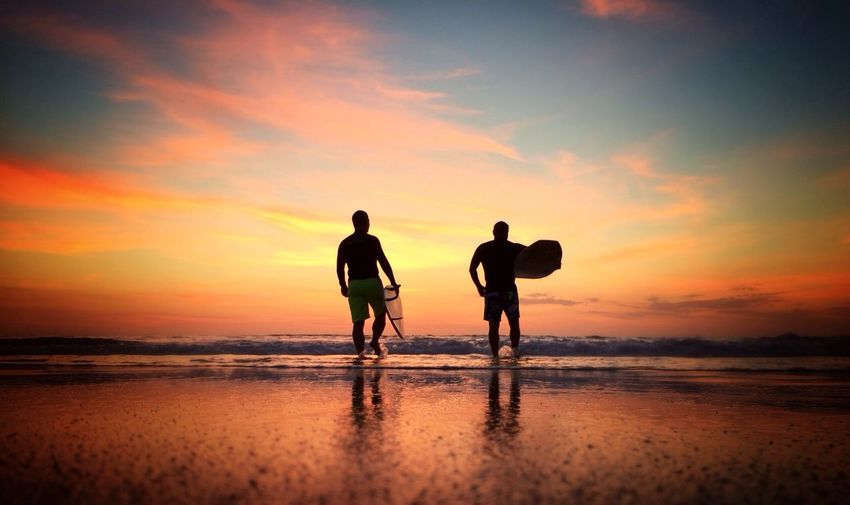 Rear view of men with surfboards walking in sea at sunset
