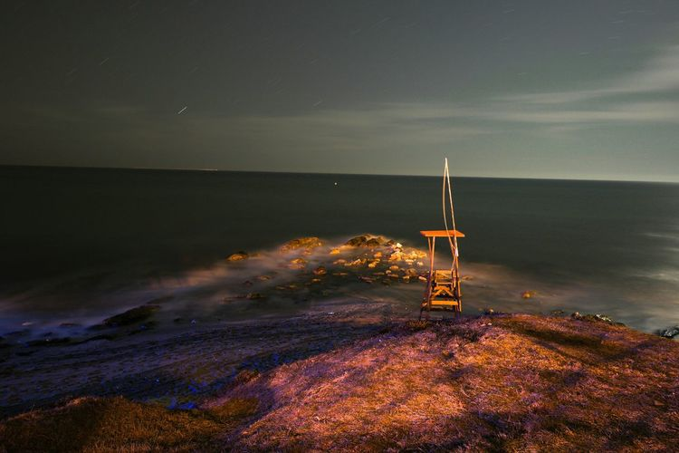 Lifeguard chair on rock by sea against sky