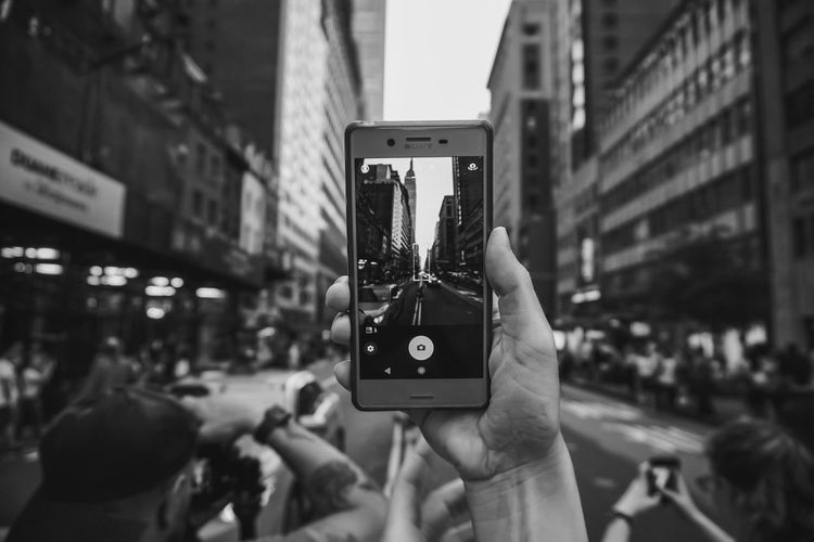 Mobile phone against modern buildings in city