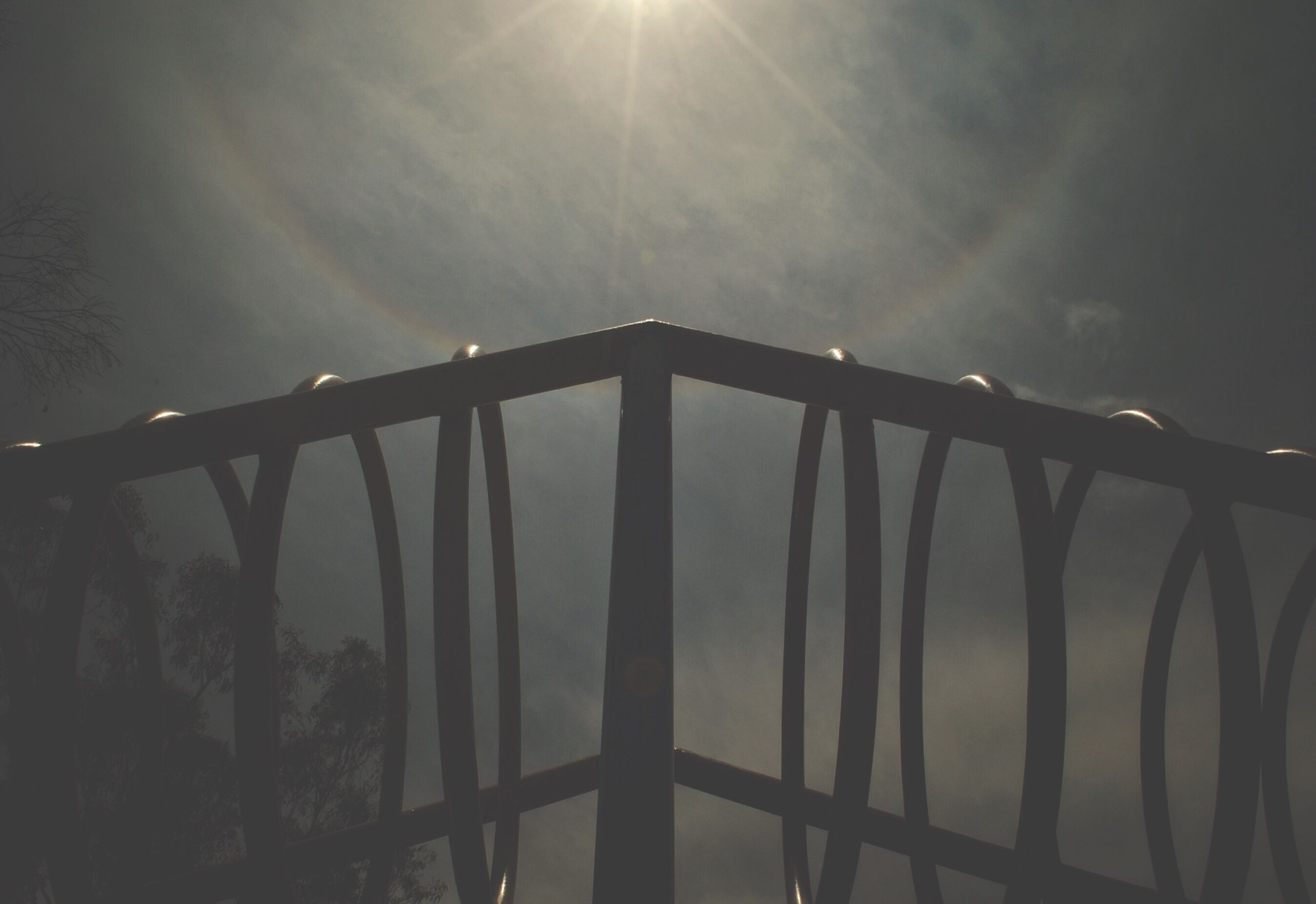 low angle view, sun, sky, sunlight, sunbeam, lens flare, built structure, metal, nature, cloud - sky, silhouette, tranquility, architecture, no people, outdoors, day, fence, protection, railing, sunset