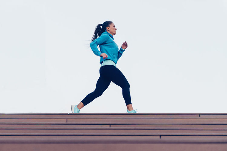 Woman Jogging Outdoors Sport Woman Female One Person Only Lifestyle Blue Urban Scene Physical Activity Motion Effort Squat Outdoors City Exercising Sports Clothing Workout Sports Training Wooden Dock Energy Athlete Caucasian Ethnicity Young Jogging Running Sport Woman
