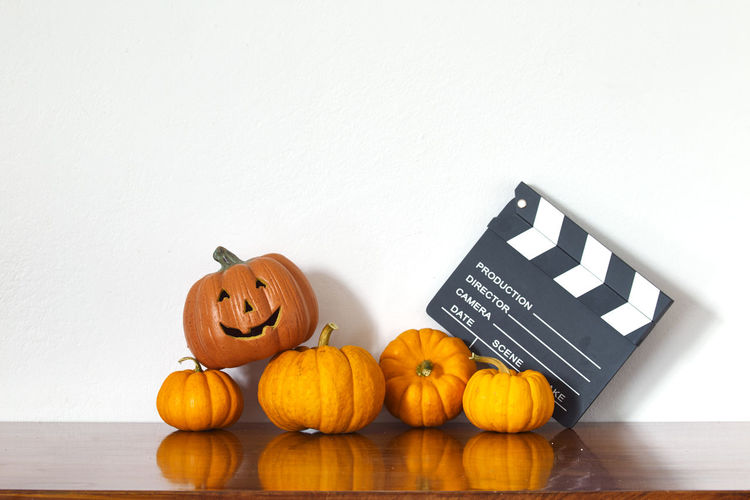 Jack o lantern with pumpkins and film slate on table against white wall