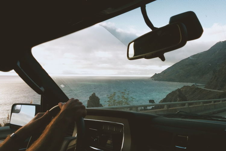 Cropped hand of man driving car on road by sea