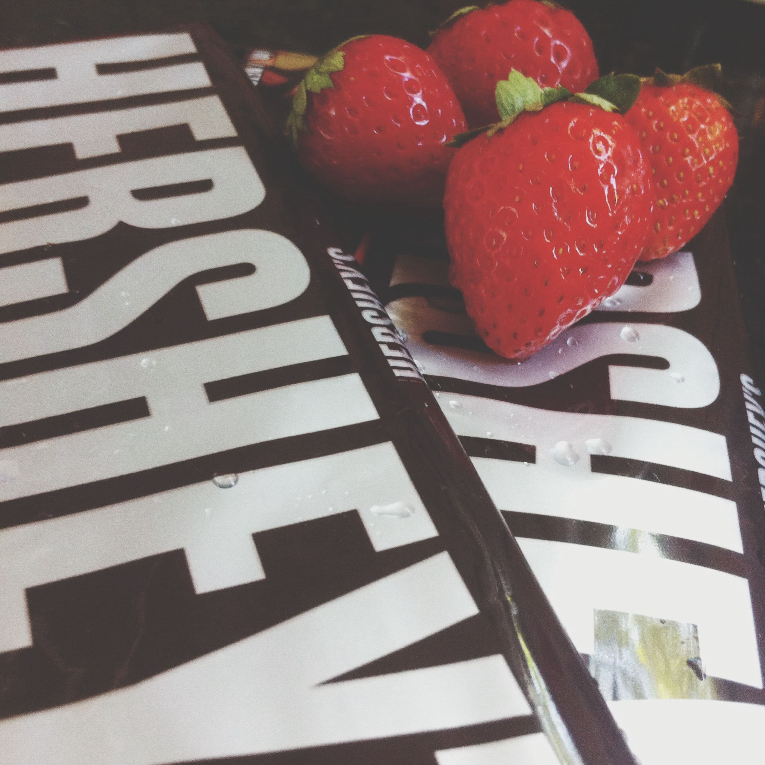 red, close-up, text, indoors, freshness, high angle view, western script, food and drink, no people, day, communication, table, water, food, fruit, focus on foreground, still life, strawberry, built structure