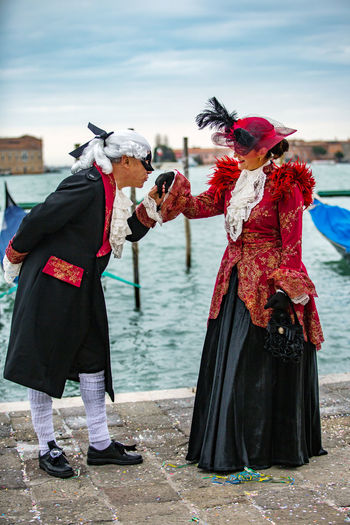 Couple In Costume Standing At Harbor During Venice Carnival