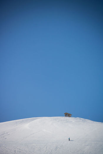 Snow covered mountain against clear blue sky