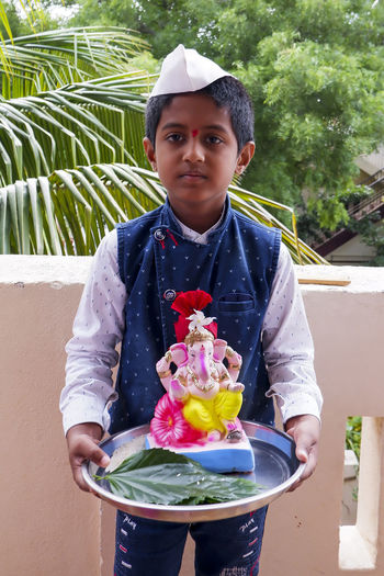Portrait of boy holding ganesh statue standing at balcony